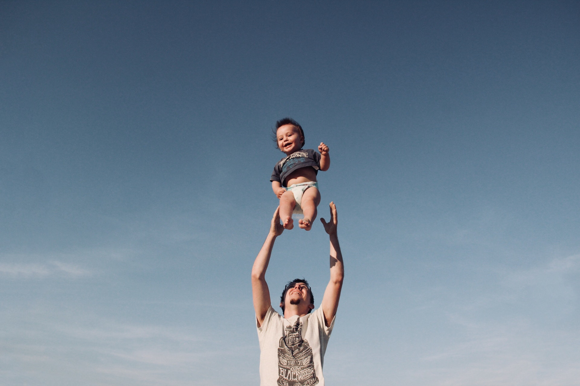 photo of man throwing up baby in air
