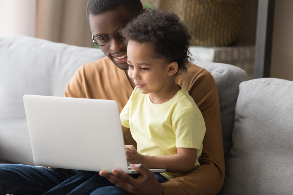 African father holds little son on lap family sitting on sofa at home with notebook, looking at screen watching cartoon educational videos, make video call, having fun enjoy free time together concept
