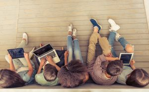 Top view of group of teenage boys and girls using gadgets while sitting in row on wooden floor